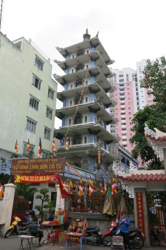 Une femme chinoise regardant son smartphone devant deux temples bouddhistes différentsau Vietnam
