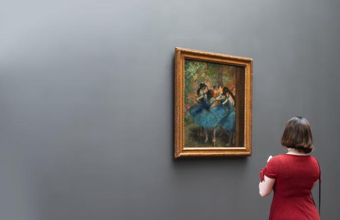 Une femme vêtue d'une robe rouge se tient debout dans une galerie d'art et observe une peinture d'Edgar Degas représentant des ballerines