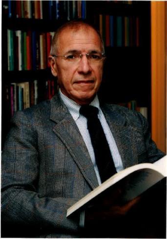 Portrait d'un homme devant une bibliothèque et tenant un livre