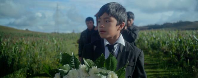 Photographie extraite du film Aya, on y voit un jeune garçon tenir un bouquet de fleurs
