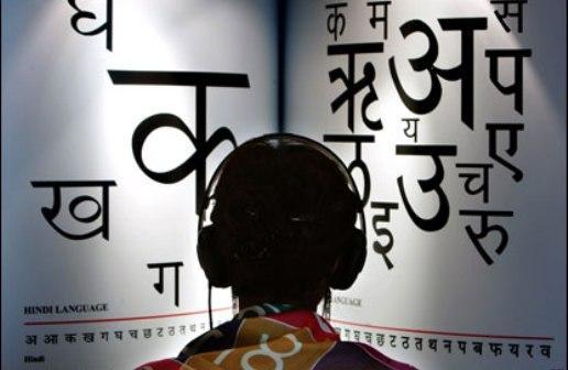 Un étudiant face à un livre en hindi surdimensionné, un casque sur la tête