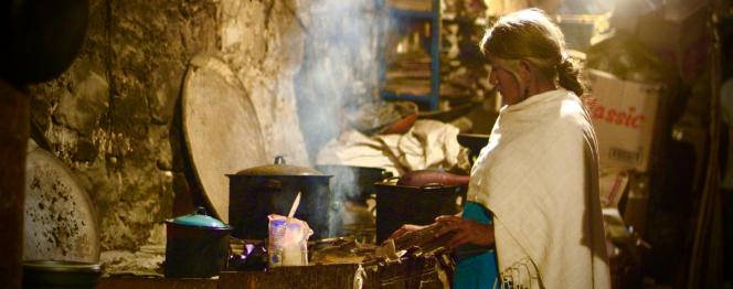 Photographie tirée du film Café, représente une femme âgée préparant à manger