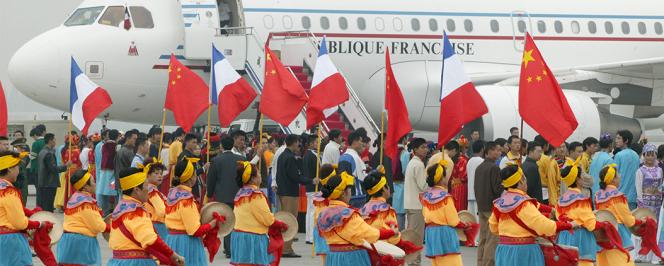 Défilé de musiciens en costumes traditionnels drapeaux chinois et français pour la cérémonie de départ