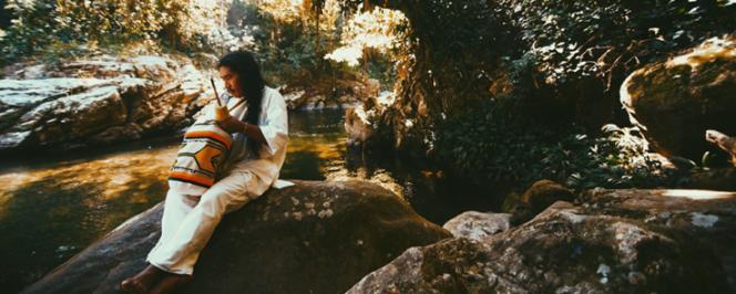 Photographie d'un homme assis sur un rocher regardant le fleuve en Colombie