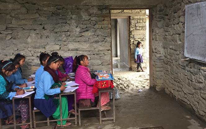 Jeunes collégiennes népalaises sur les bancs d'une école en train de recopier une leçon au tableau