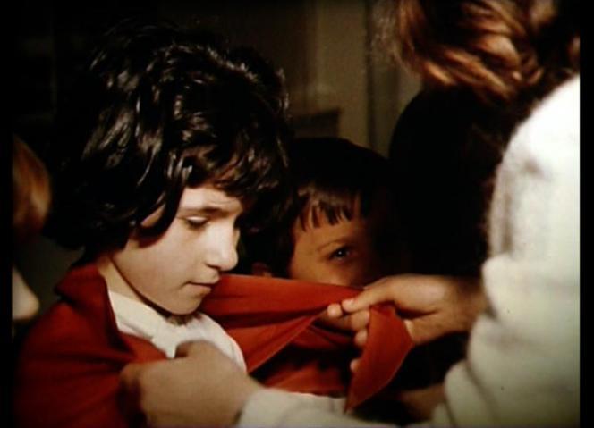 Gros plan sur deux mains de femme qui tiennent un foulard autour du cou d'un jeune garçon.