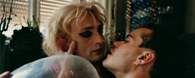 Un homme enbrasse un homme travesti avec un préservatif gonflé au premier plan