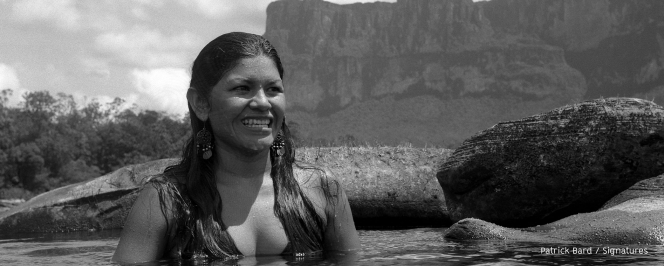 Femme autochtone se baignant dans un lac au milieu des montagnes