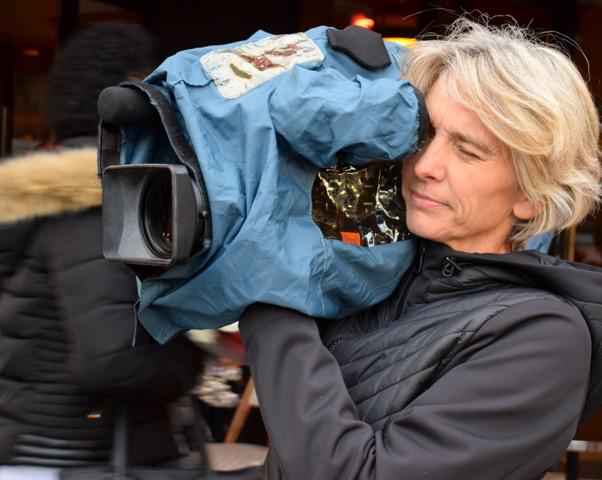 Sandrine Loncke, une caméra sur l'épaule, en train de filmer