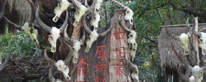 Photographie d'un édifice érigé en 2016 à l'entrée du village touristique wa de Wengding sur lequel est gravé en caractères chinois « Wengding, dernière tribu primitive de Chine » (Crédit : Sarah Coulouma)