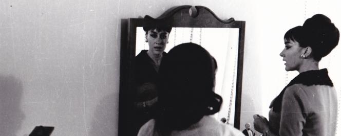 Photographie en noir et blanc. Deux femmes de dos se regardant dans un miroir
