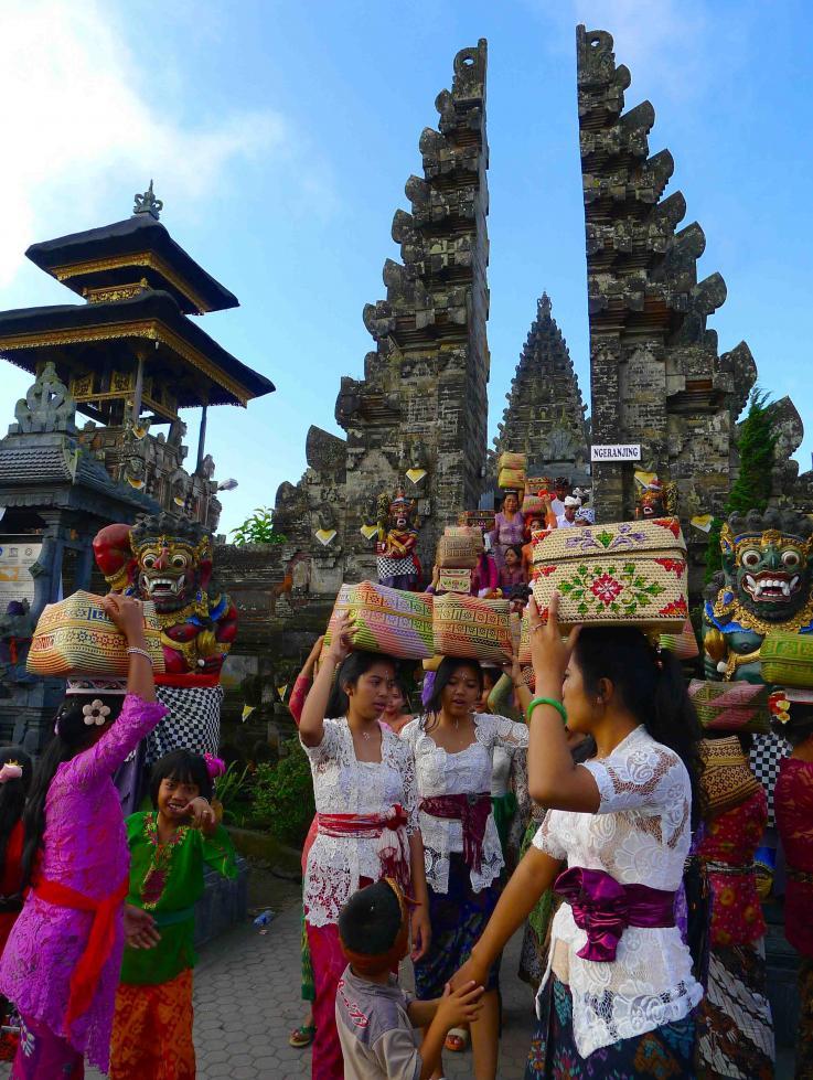 Après la culte, sortie des fidèles (femmes) portant leurs offrandes du temple de l'amont du lac Batur à Bali (Indonésie)