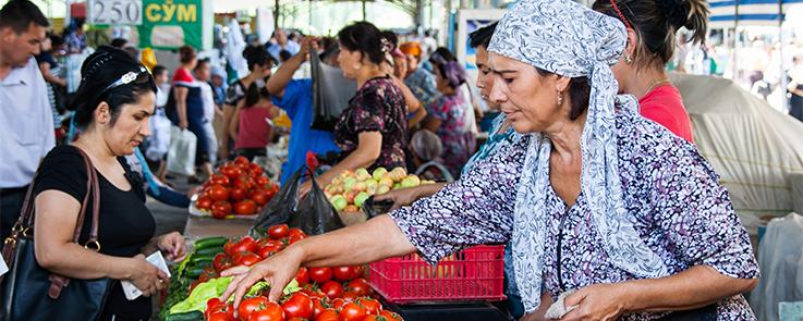 Femme ouzbek déposant des tomates sur son étal lors d'un marché à Tachkent, Ouzbékistan
