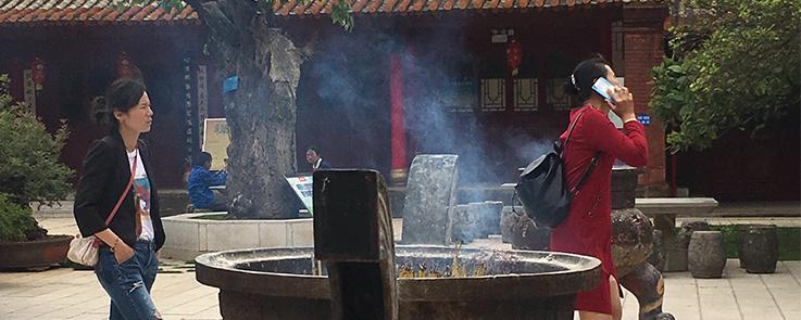 Passants sur la place du temple Qiongzhu en Chine, avec en premier plan un chaudron chinois fumant.