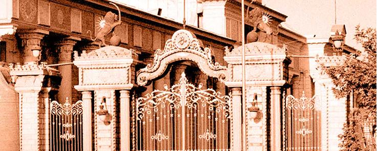 Portail avec une grille en fer forgé et deux piliers, chacun surmonté d'un lion.