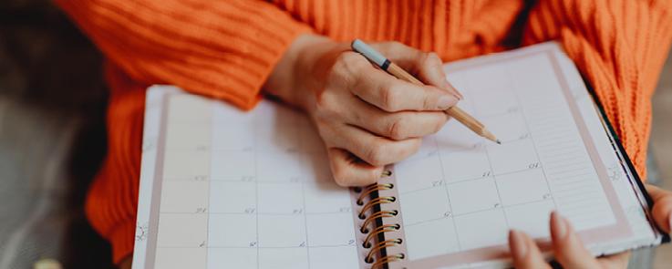 Photographie représentant une femme écrivant sur un agenda