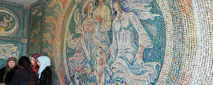 groupe de femmes devant une fresque en mosaïque représentant la maternité