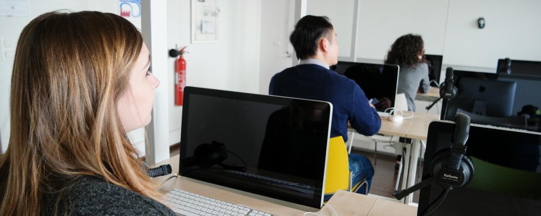 Trois étudiants sont devant des ordinateurs durant un cours