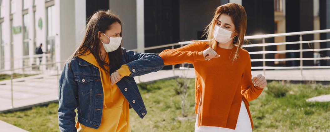 Deux jeunes filles portant un masque chirurgical se saluant avec le coude