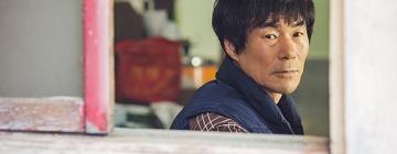 Portrait d'un homme coréen regardant à l'extérieur par la fenêtre ouverte
