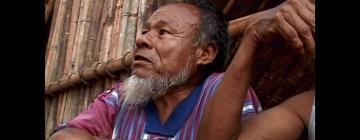 Bicicletas de Ñanderú - Photographie d'un homme assis près d'une cabane, regardant devant lui