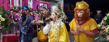 Personnages en costume traditionnels chinois célébrant le moine Xuanzang. Un des personnages porte un masque de singe.