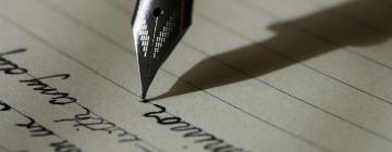 Pointe de stylo-plume qui trace des lettres sur papier