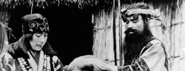 Couple Aïnou vêtus d'une tenue traditionnelle en compagnie d'un ourson.