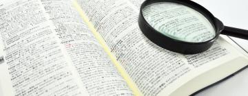 un dictionnaire japonais-anglais avec une loupe posée dessus