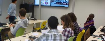 Cinq étudiants en classe et une enseignante de bout tournée vers un tableau en deux volets. Sur celui de gauche on aperçoit le contenu du cours. Sue celui de droite une classe à distance en visioconférence.
