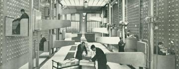Salle d'archives en noir et blanc avec des personnes travaillant