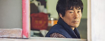 Homme coréen regardant par la fenêtre