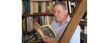 """Thomas Szende assis sur les marches de sa bibliothèque,  feuillette """"L'homme sans qualités"""" de Robert Musil."""